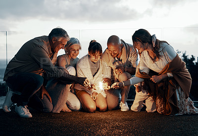 Buy stock photo Full length shot of an affectionate family lighting up sparklers while celebrating a new year outdoors
