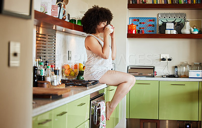 Buy stock photo Shot of an attractive young woman have a cup of coffee in the kitchen at home