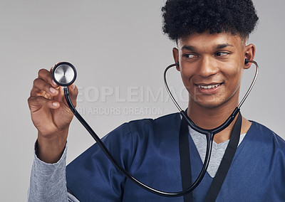 Buy stock photo Shot of a male nurse holding up a stethoscope while standing against a grey background