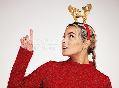 Buy stock photo Studio shot of a young woman pointing against a grey background