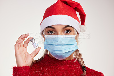 Buy stock photo Studio shot of a young woman holding vaccine and wearing a mask against a grey background