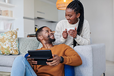 Buy stock photo Shot of a young couple using a digital tablet while relaxing together at home