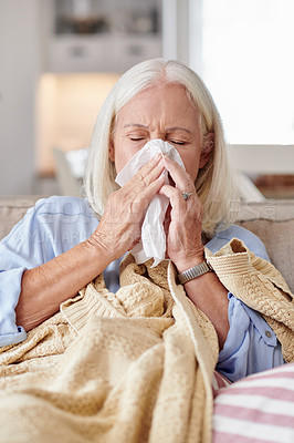 Buy stock photo Shot of a senior woman blowing her nose while feeling sick at home