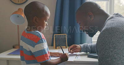 Buy stock photo Shot of a mature man helping his grandson with his homework at home