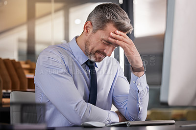 Buy stock photo Shot of a businessman suffering from a headache while sitting at his desk