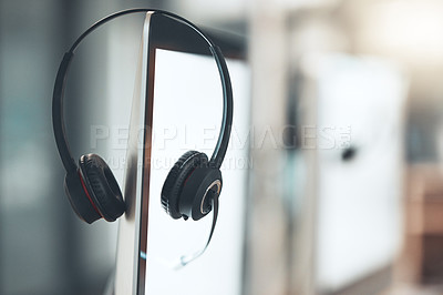 Buy stock photo Shot of a pair of headsets sitting on the edge of a computer screen in an empty office