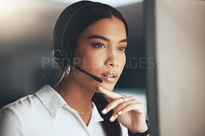 Buy stock photo Shot of a young call centre agent sitting alone in the office and looking contemplative while using her computer