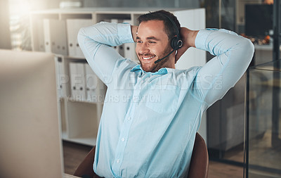 Buy stock photo Shot of a young call centre agent sitting in the office with his hands behind his head and feeling accomplished