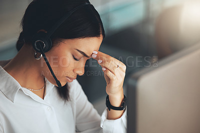 Buy stock photo Shot of a young call centre agent sitting alone in her office and feeling stressed