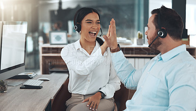 Buy stock photo Shot of two young call centre agents sitting in the office together and celebrating a success