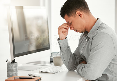 Buy stock photo Shot of a young businessman suffering from a headache in an office at work