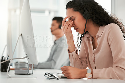 Buy stock photo Shot of a young female call center agent suffering from a headache in an office at work