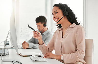 Buy stock photo Shot of a young female call center agent using a computer at work