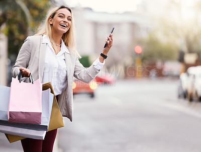 Buy stock photo Cropped shot of an attractive young woman checking her cellphone to see whereabout her cab is while out shopping in the city