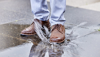 Buy stock photo Shot of a unrecognizable man walking in a puddle of water outside