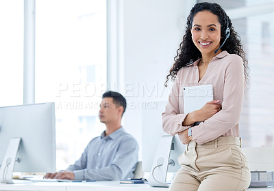 Buy stock photo Shot of a young call centre agent sitting and holding a digital table while her colleague works behind her