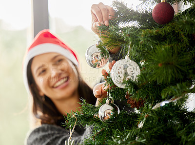 Buy stock photo Shot of a young woman wearing a Christmas hat at home