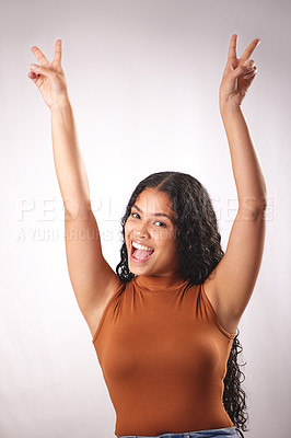Buy stock photo Studio shot of a beautiful young woman showing the peace sign