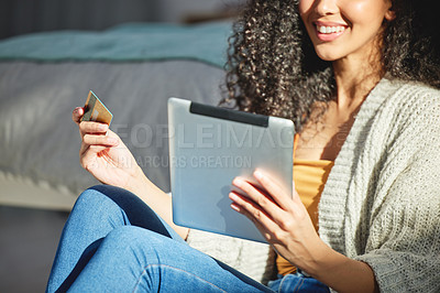 Buy stock photo Shot of a young woman using her digital tablet to make online card payments