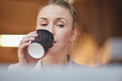 Buy stock photo Low angle shot of an attractive young businesswoman drinking a coffee while working at her desk in the office