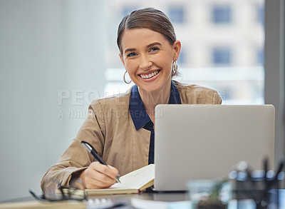 Buy stock photo Shot of an attractive young businesswoman sitting alone in her office and writing notes