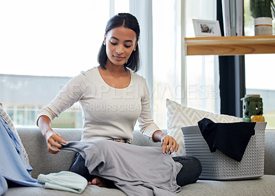Buy stock photo Shot of a young woman folding laundry at home