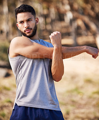 Buy stock photo Shot of a handsome young man standing alone outside and stretching before going for a run