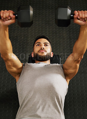 Buy stock photo Shot of a young man working out with dumbbells in a gym