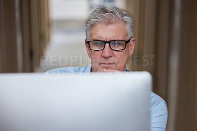 Buy stock photo Shot of a mature businessman sitting alone in the office and using his computer