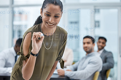 Buy stock photo Shot of a young businesswoman writing notes on a glass screen during a meeting in an office