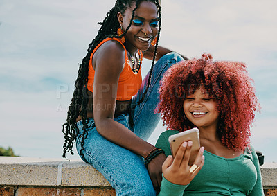 Buy stock photo Shot of two young friends using a phone in the city