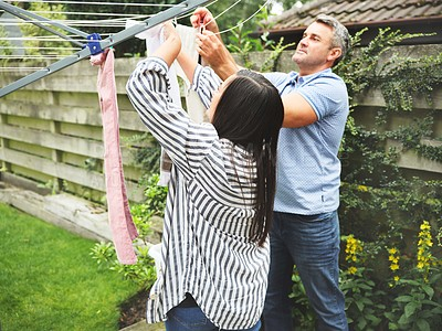 Buy stock photo Shot of a couple hanging washing in their yard at home