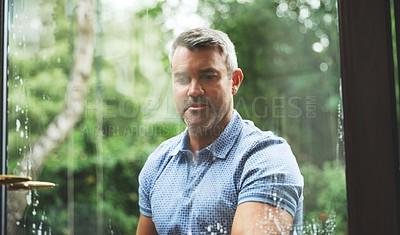 Buy stock photo Shot of a mature man washing windows at home
