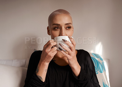 Buy stock photo Shot of a young woman enjoying a cup of coffee while relaxing at home