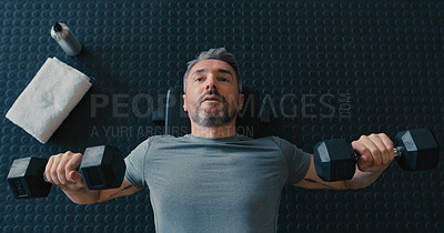 Buy stock photo Shot of a mature man lying down and using dumbbells for chest press exercises in the gym