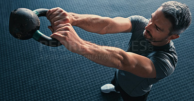 Buy stock photo Shot of a mature man standing alone and using a kettle bell during his workout in the gym