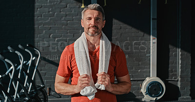 Buy stock photo Shot of a handsome mature man standing alone after his workout in the gym