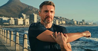 Buy stock photo Shot of a mature man stretching his arms while exercising along the promenade