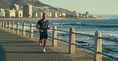 Buy stock photo Shot of a mature man running along the promenade
